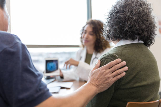 man with hand on woman's shoulder talking to healthcare professional over desk